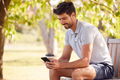 Man Wearing Summer Shorts Sitting On Park Bench Under Tree With Takeaway Coffee Using Mobile Phone - PhotoDune Item for Sale