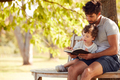 Father Sitting On Park Bench Under Tree With Son Reading Book Together - PhotoDune Item for Sale