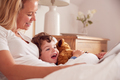 Mother In Bedroom Looking At Picture Book With Young Son Wearing Pyjamas Cuddling Soft Toy - PhotoDune Item for Sale