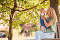 Loving Mother Cuddling And Playing With Baby Daughter Outdoors Sitting On Seat Under Summer Tree - PhotoDune Item for Sale