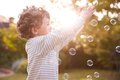 Young Boy Having Fun In Garden Chasing And Bursting Bubbles - PhotoDune Item for Sale