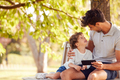Father Sitting On Park Bench Under Tree With Son Looking At Mobile Phone Together - PhotoDune Item for Sale