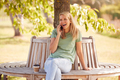 Woman Sitting Bench Under Tree In Summer Park Chatting On Mobile Phone - PhotoDune Item for Sale