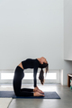 Woman practicing camel pose (Ustrasana) during a yoga session at home - PhotoDune Item for Sale