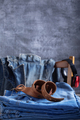 Denim jeans at old wooden chair near grey wall background texture - PhotoDune Item for Sale