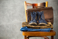 Denim jeans and old boots shoes with leather bag at old wooden chair - PhotoDune Item for Sale