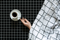 Caffeine and sleep problems. Drinking coffee before bed. A cup of black coffee on black checkered - PhotoDune Item for Sale