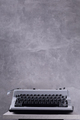 Vintage typewriter at wooden top table or shelf near wall background surface - PhotoDune Item for Sale