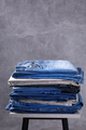 Denim jeans at chair or shelf of rack near grey wall background texture - PhotoDune Item for Sale