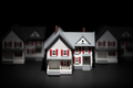 Several Model Houses In A Row With One Spot Lit In The Front - PhotoDune Item for Sale