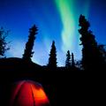 Orange taiga tent glow under northern lights flare - PhotoDune Item for Sale