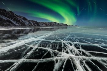 Aurora borealis over a rock in a frozen lake