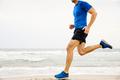 closeup male runner running sandy beach - PhotoDune Item for Sale