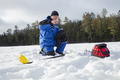 Man ice fishing on a northern Minnesota lake on a sunny winter morning - PhotoDune Item for Sale