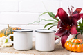Placeit-Two white campfire enamel mug mockup with pumpkin and lily - PhotoDune Item for Sale