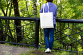 Placeit - Woman in blue jumper holding tote bag mockup - PhotoDune Item for Sale