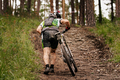 dirty cyclist with mountain bike uphill - PhotoDune Item for Sale