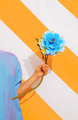 Unrecognizable model on trend striped yellow background with flower  in her hands. - PhotoDune Item for Sale