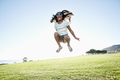 Young mixed race girl with long curly hair leaping in the air - PhotoDune Item for Sale
