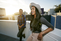 Two young women on a rooftop at sunset, lens flare, city buildings in the background - PhotoDune Item for Sale