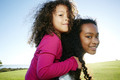 Young mixed race girl giving a younger sister a piggyback - PhotoDune Item for Sale