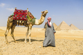 Three pyramids, and tourist guide with camel - PhotoDune Item for Sale