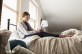 Teenage girl sitting on her bed using her smart phone - PhotoDune Item for Sale