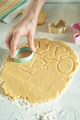 Female model cut dough with cookie cutter on kitchen table - PhotoDune Item for Sale