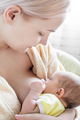 Caucasian blonde young mother breastfeeding her baby vertical photo. - PhotoDune Item for Sale