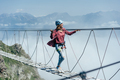 A happy cheerful woman walks on a suspension bridge high in the mountains. - PhotoDune Item for Sale