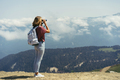 woman with a backpack in the mountains looks at the landscape through binoculars. - PhotoDune Item for Sale