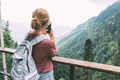 Young confident woman with a backpack in the mountains taking picture on camera of mobile phone. - PhotoDune Item for Sale