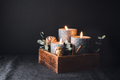 New Year festive decorations with wooden box and black burning candles in a dark interior. - PhotoDune Item for Sale