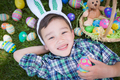 Mixed Race Chinese and Caucasian Boy Outside Wearing Rabbit Ears Playing with Easter Eggs - PhotoDune Item for Sale