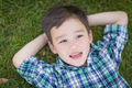 Thoughtful Mixed Race Chinese and Caucasian Young Boy Relaxing On His Back Outside On The Grass - PhotoDune Item for Sale
