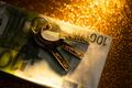 keys and money banknotes on golden background - PhotoDune Item for Sale