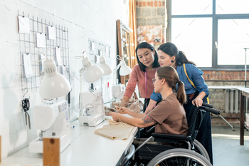 Two young female fashion designers consulting with seamstress in wheelchair during discussion