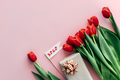 Festive spring flower background. On the pink surface lies a gift, red tulips, space for text. - PhotoDune Item for Sale