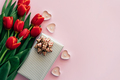 Pink background with place for text with red fresh flowers tulips gift box and heart shaped candles. - PhotoDune Item for Sale
