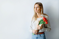 Young charming woman stands against a white wall with a bouquet of tulips, place for text - PhotoDune Item for Sale