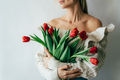 A young woman holds a gorgeous bouquet of red tulips in her hands. Festive flower spring concert. - PhotoDune Item for Sale