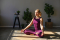 Attractive woman in sportswear sitting on the floor in lotus position meditation at home. - PhotoDune Item for Sale