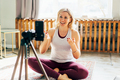Athletic female fitness and yoga blogger in sportswear recording video of training on mobile - PhotoDune Item for Sale