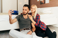 A young couple sitting on the floor in the room makes a selfie on a mobile phone. - PhotoDune Item for Sale