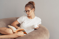 Cute girl is drinking coffee and reading a book - PhotoDune Item for Sale
