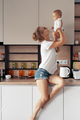 Young mother with baby in the kitchen - PhotoDune Item for Sale