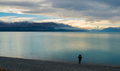 Rear view of a Person Standing by a Lake Watching the Sunset Against a Cloudy Sky and Snow Mountains - PhotoDune Item for Sale