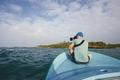 Traveler with camera sitting on boat against beautiful coast - PhotoDune Item for Sale
