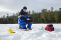 Man ice fishing on a northern Minnesota lake on a winter morning - PhotoDune Item for Sale