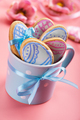 Easter baking background of frosted cookies in shape of egg in blue mug on pink background - PhotoDune Item for Sale